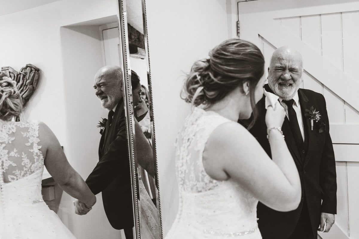 A black and white shot of bride and her father. She is crying happily with a tissue to her eye. He is smiling proudly.