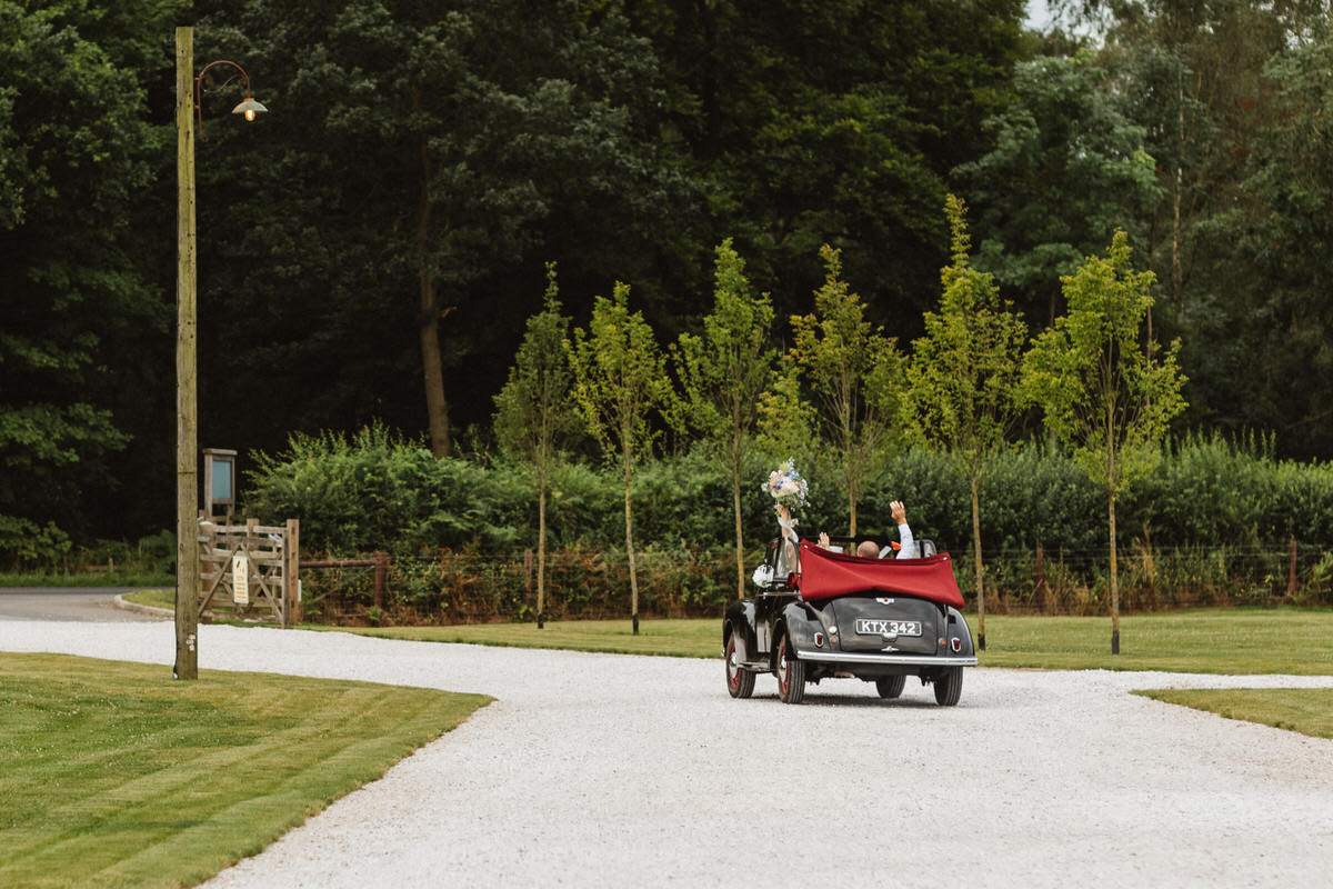 A couple waving out of an open-top vintage black car. Do I travel? One of the best questions to ask a wedding photographer