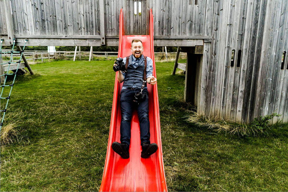 Me smiling with a camera in my hand coming down a red slide. I'm having way too much fun!
