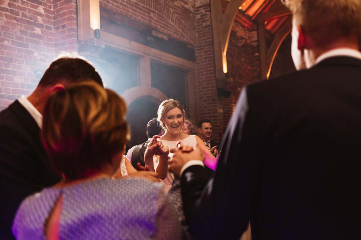 This is one of the best questions to ask a wedding photographer. An image of a smiling bridesmaid on a packed dance floor.