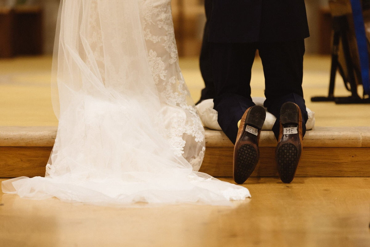 """A bride is kneeling at the church. The groom has stuck """"help"""" and """"me"""" to the underside of his shoes."""