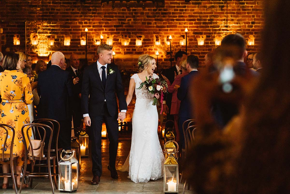 Couple smiling at their guests as they walk down the aisle at Hazel Gap Barn.