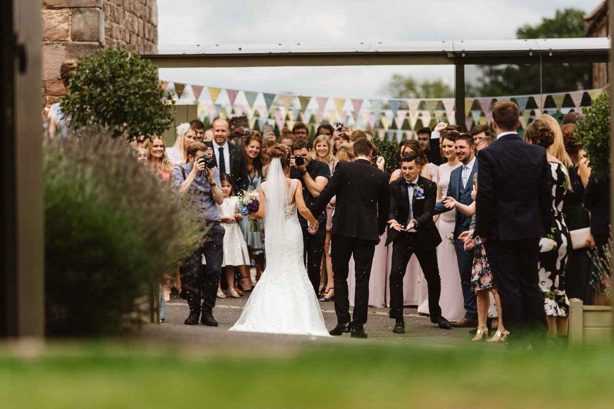 A couple shot from behind as they walk into a crowd of guests for their confetti. I'm in the shot with the videographer.
