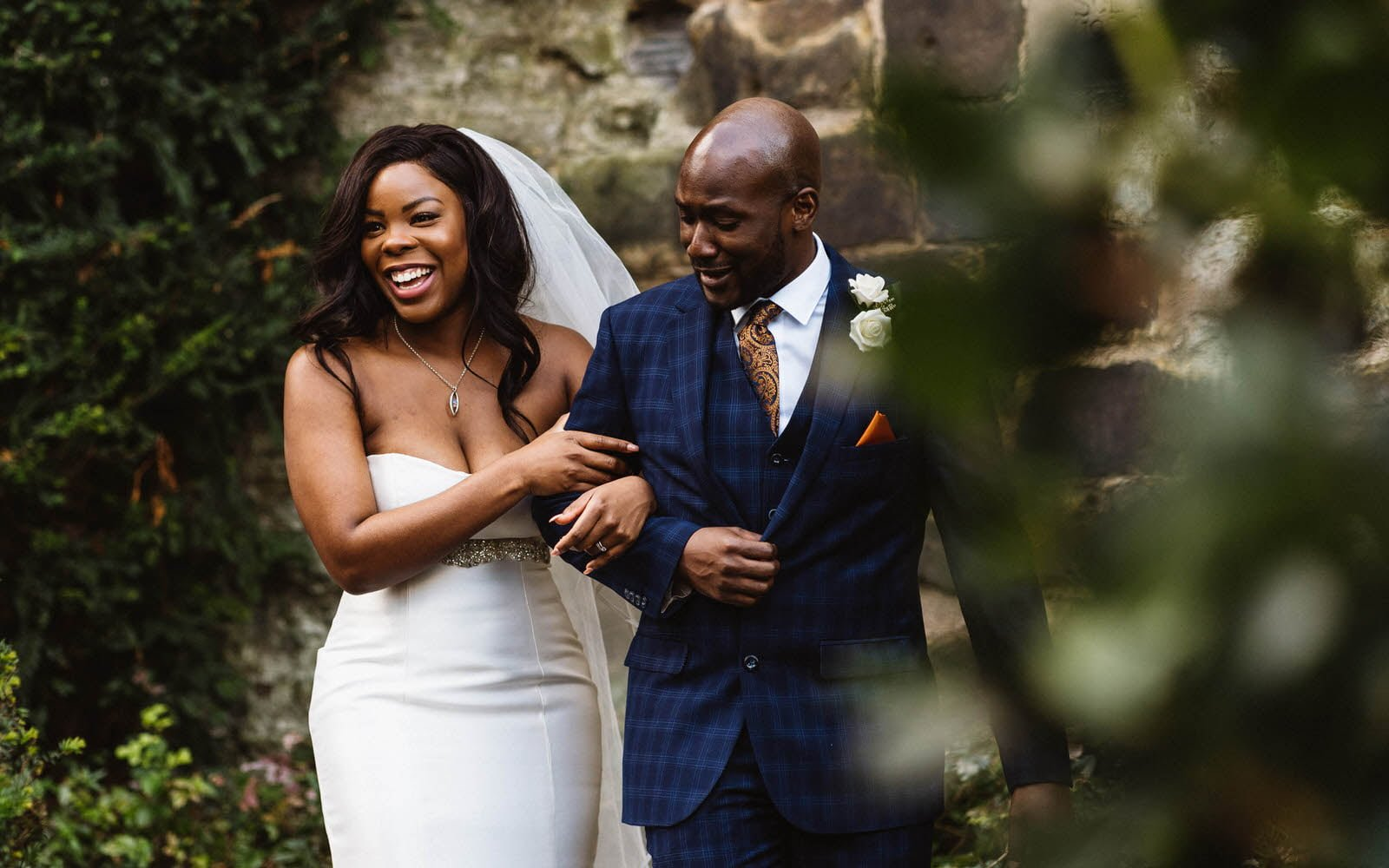 A couple arm in arm walking. The bride is stunning and beaming with joy and the groom looks dapper.