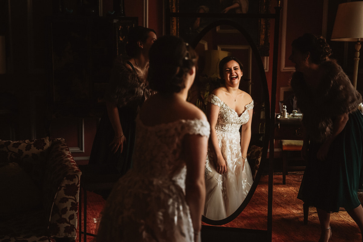 Reflection of Bride laughing in a mirror at Thrumpton Hall before she gets married at St Nic's Church.