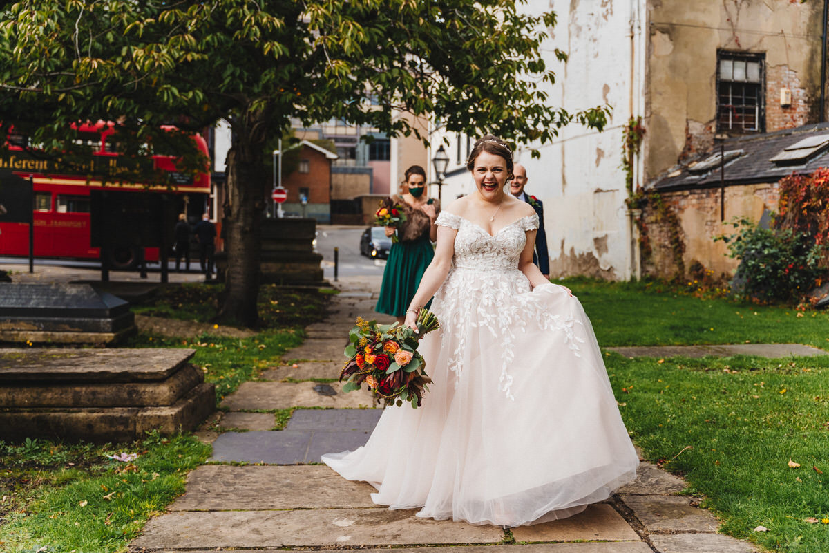 Bride laughing as she walks through St Nic's Church garden on her way to get married.
